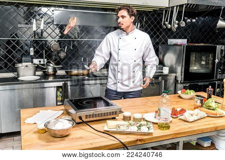 chef tossing up meat with frying pan