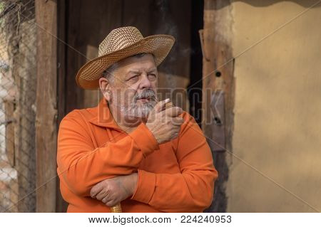 Nice portrait of Ukrainian bearded senior man in straw hat sitting against old barn  entry with tobacco-pipe