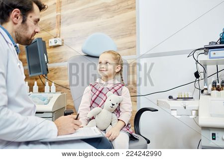 Happy adorable child with toy talking to doctor and listening to his advice