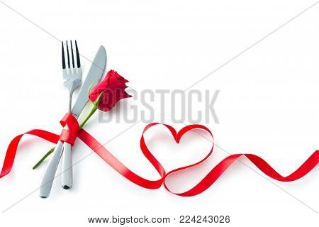 Silverware tied up with red ribbon in heart shape isolated on white background. Concept Valentines Day dinner. Restaurant party celebration