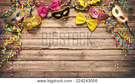 Colorful carnival or party frame of masks, streamers and confetti on a rustic wood background with copy space for your greeting, invitation or advertising