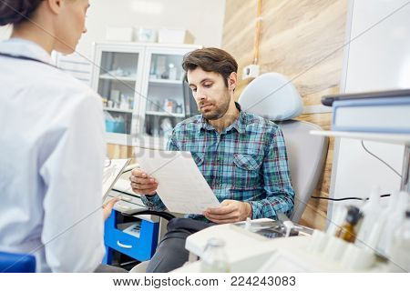 Young patient reading notes of doctor and prescriptions on paper