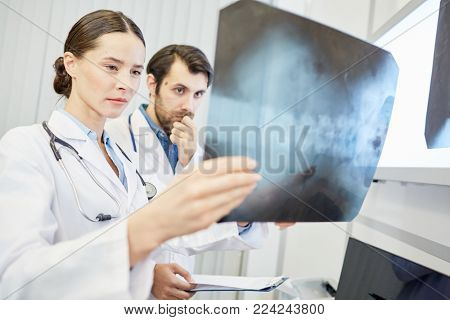Young radiologist looking at x-ray image result with her colleague near by