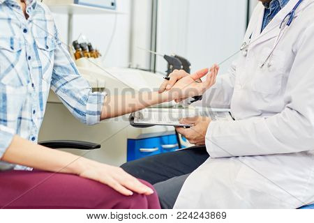 Young therapeutist checking pulse of his patient during appointment