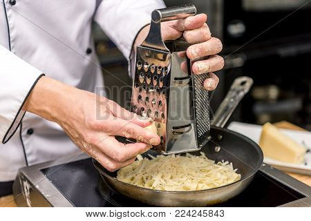 cropped image of chef grating cheese on grater
