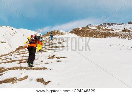 A group of three freeriders climb the mountain for backcountry skiing along the wild slopes of the North Caucasus. The concept of backcountry freeride. North Caucasus. Russia