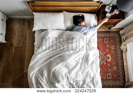 Asian woman on the bed waking up by the alarm clock