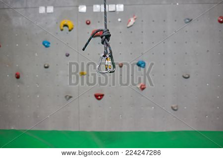 Tight climbing rope with two metallic hooks tied by knot hanging over green mat