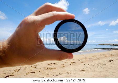 Polarizing Filter Hold Against The Beach Giving Clarity. Optics Tool For Lens In Photography
