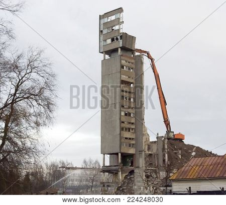 Dismantling of the remains of the high rise building by means of the excavator
