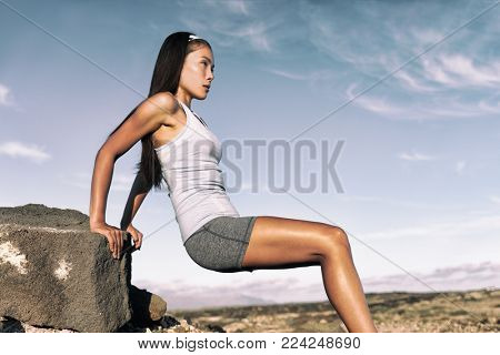 Strength training fitness woman working out arms muscles doing triceps dips. Asian athlete exercising with bodyweight exercises for toned body.