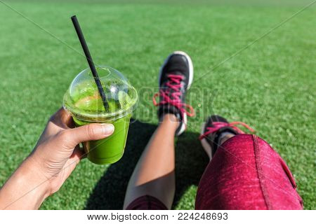 Green smoothie detox fitness girl drinking plastic cup take-out morning breakfast juice during run in summer park. Healthy lifestyle sport person POV of hand holding drink with running shoes selfie.