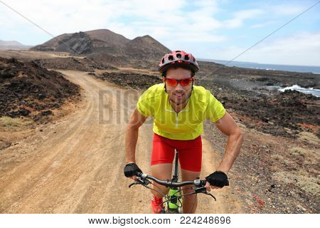 Mountain biking MTB bike man riding bicycle on dirt road in mountain trail outdoor. Sport fitness man in helmet, sunglasses, gloves active lifestyle.