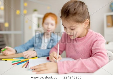 Diligent girl with crayon drawing at lesson while her classmate looking at her notepad