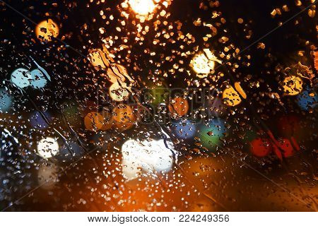 Rain drops on the window. Rain drops on the glass on a background of a night blurred city. Rainy weather. Outside the window is a blurred city. Bokeh night city.