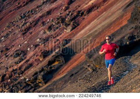 Man trail running in mountains. Runner on outdoor run. Fitness and health active lifestyle.