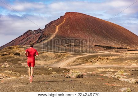 Sport and fitness athlete running on mountain trail, man active lifestyle. Man runner on long distance run through desert summer landscape.