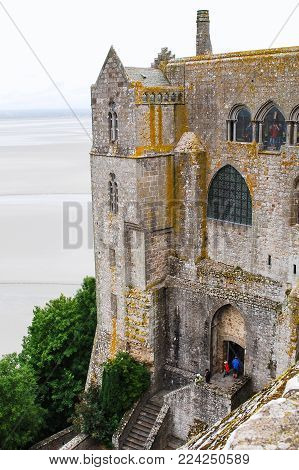 LE MONT SAINT-MICHEL - JULY 5, 2010: visitors in castle building of Saint Michael Abbey. Le Mont Saint-Michel is an island commune in Normandy, first monastic on the mount was built in the 8th century