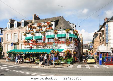 PAIMPOL, FRANCE - JULY 6, 2010: people walk near restaurants on street Quai Morand in Paimpol city. Paimpol is a commune in the Cotes-d'Armor department in Brittany on coast of English Channel.