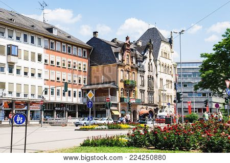 TRIER, GERMANY - JUNE 28, 2010: people near houses along Porta--Platz square in Trier city. The town was founded by the Celts in the late 4th century BC as Treuorum