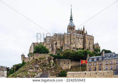 LE MONT SAINT-MICHEL - JULY 5, 2010: view of Saint Michael's Abbey on top of mount in rainy day. Le Mont Saint-Michel is an island commune in Normandy