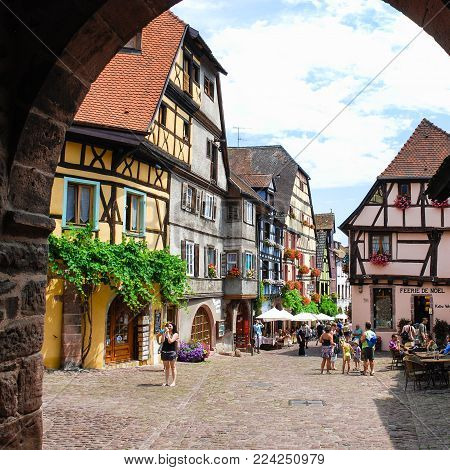RIQUEWIHR, FRANCE - JULY 11, 2010: visitors on square of Riquewihr town. Riquewihr is commune in Alsace Wine Route region, the town belongs to the association The most beautiful villages of France