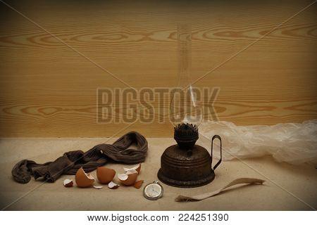 old kerosene lamp clock stocking and egg shell on a light background