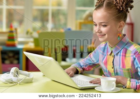 Portrait of cute little girl sitting at the table with laptop