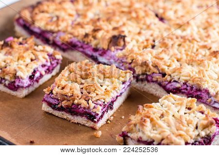 Homemade shortcrust fruit pie with crumble on a baking sheet - pastry with fruit or berry (cherry, plum, strawberry, raspberry) jam for tea time