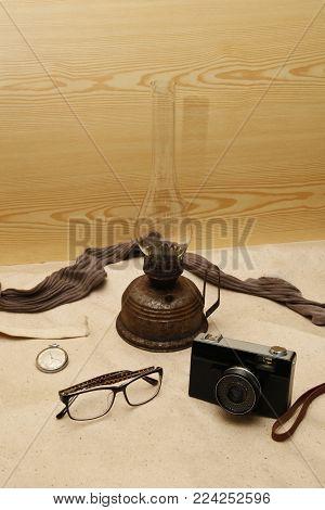 old kerosene lamp clock stocking camera and glasses on a light background