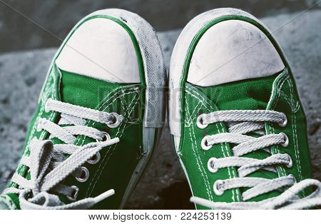 Feet in dirty green sneakers and jeans outdoors. Making first step.