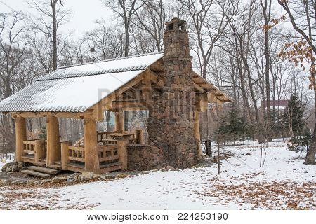 Wooden patio shelter with fireplace. Winter landscape in the park.