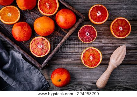 Sliced And Whole Ripe Juicy Blood Oranges And Grapefruit In The Box On Wooden Background.