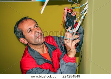 Electrician Using a Digital Multimeter. Electrician installs wiring in new apartment.  Wiring an Outlet to an Electrical Box.