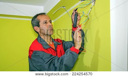 Electrician Measuring With a Digital Multimeter. Electrician installs wiring in new apartment. Wiring an Outlet to an Electrical Box.