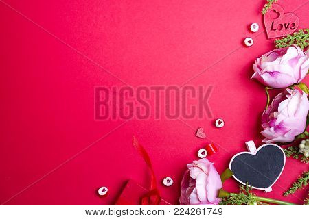 Frame from flowers, heart candies and heart chalk board on red background with copy space. Concept for valentine's day love celebration.