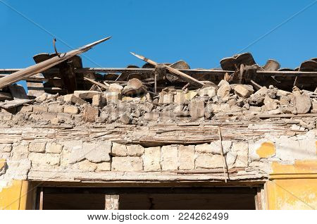 Small old and abandoned house roof demolished by the earthquake destruction closeup with blue sky background