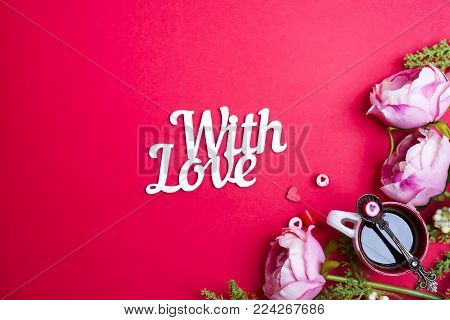 Red candy heart shape on spoon on a cup of coffee with flowers and lettering With Love on red background with copy space. Concept for valentine's day love celebration.