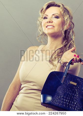 Fashion of women. Clothing and accessories. Mid aged blonde fashionable woman with handbag. Elegant lady on gray.
