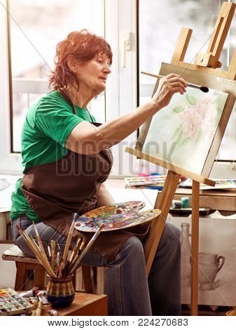 Artist painting easel in studio. Authentic senior woman has small home own business paints with brush in morning spring sunlight on window work place background.