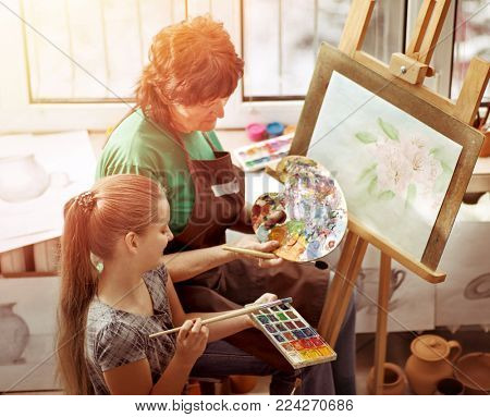 Artist painting easel in studio. Authentic grandmother and kids girl paints with palette watercolor paints palette and brush morning sunlight . Top view school interior handmade crafts with window .