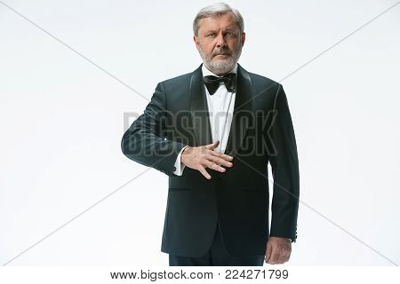 The senior waiter holding white towel and standing isolated on white studio background. sign language in the restaurant. Gesture means - carbonated water should be served