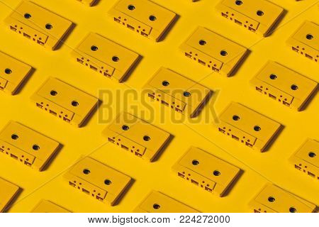 Yellow Audio Cassette Tapes On Yellow Background. Creative Concept Of Retro Technology
