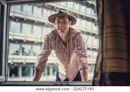 Smiling guy in big hat looking through window. Hipster style