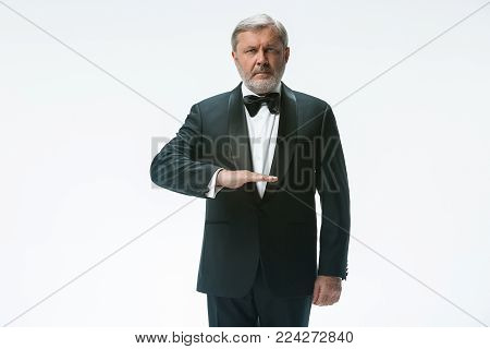 The senior waiter holding white towel and standing isolated on white studio background. sign language in the restaurant. Gesture means - distilled water should be served
