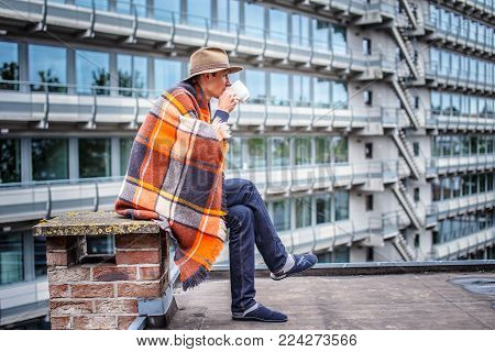 Man in blanket drinking coffe on the roof of multifamily houses.
