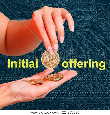 Initial coin offering on the PC circuit board. Female hands hold an electronic coin as an ICO symbol