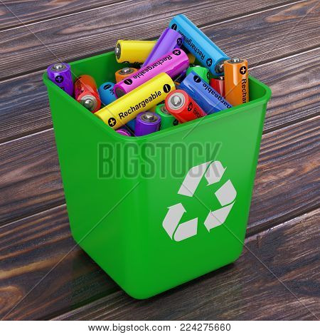 Heap of Rechargeable Batteries in Green Bucket with Recycle Sign on a wooden table. 3d Rendering