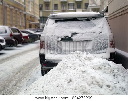 Snow pile and cars parked, concept of winter traffic collapse