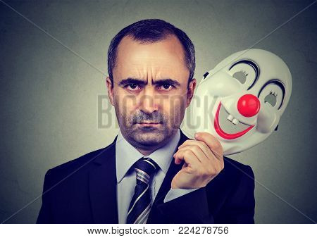 Angry business man taking off happy clown mask